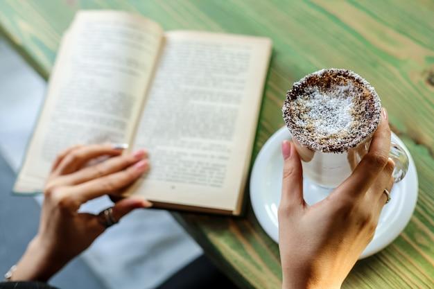 ココナッツとラテを飲んで、テーブルで本を読んでサイドビュー女性 無料写真