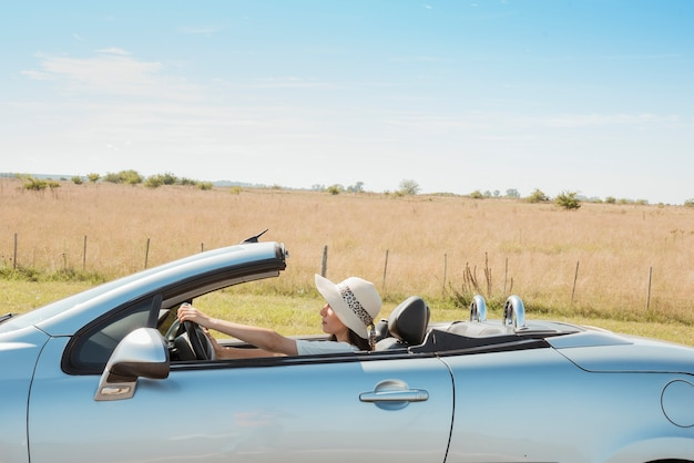 Side view of woman driving cabriolet Free Photo