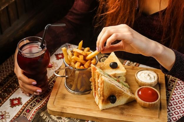 Женщина сбоку ест картофель фри с клубничным кетчупом и майонезом на подставке с безалкогольным напитком Бесплатные Фотографии