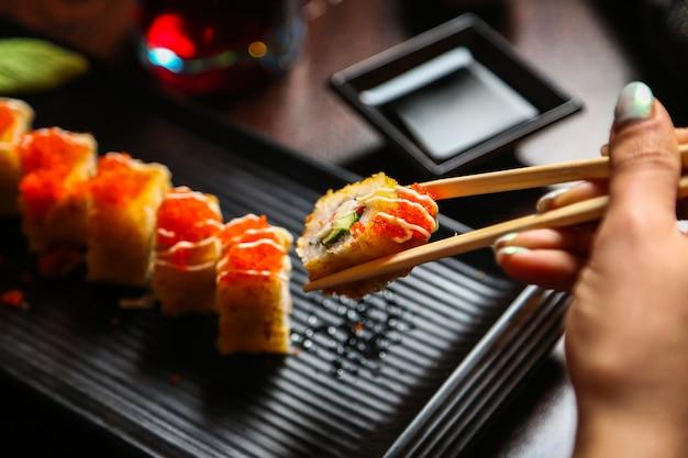 スタンドに醤油と醤油の炒め寿司を食べる女性の側面図 無料写真