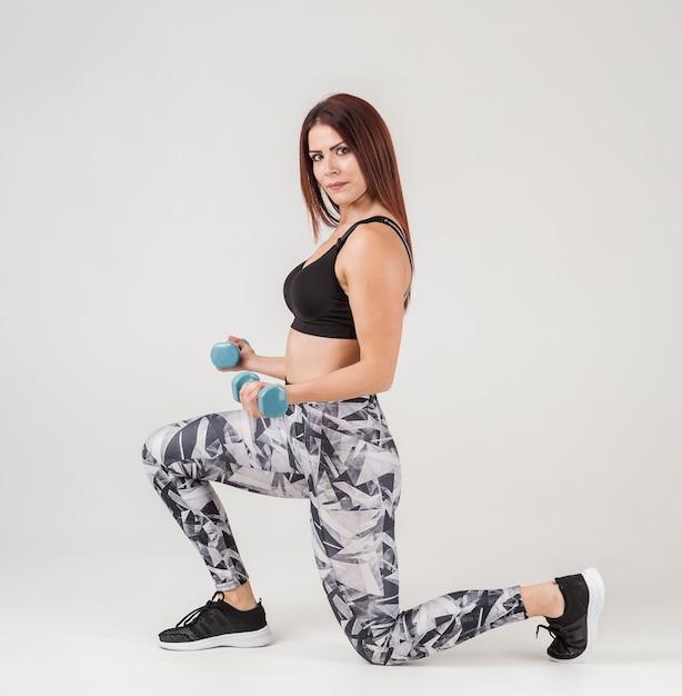 Vista laterale della donna che si esercita con i pesi Foto Gratuite