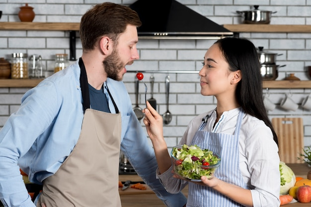 Side view of woman feeding cherry tomato her husband in kitchen