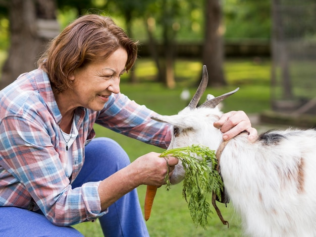 Side view woman feeding a goat with carrots Free Photo