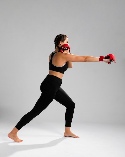 Side view woman in fitness clothes punching with box gloves Free Photo