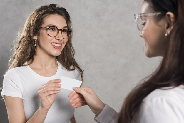 Side view of woman giving business card to potential employee Free Photo