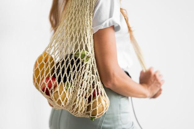 Вид сбоку женщина, держащая перерабатываемый мешок Бесплатные Фотографии