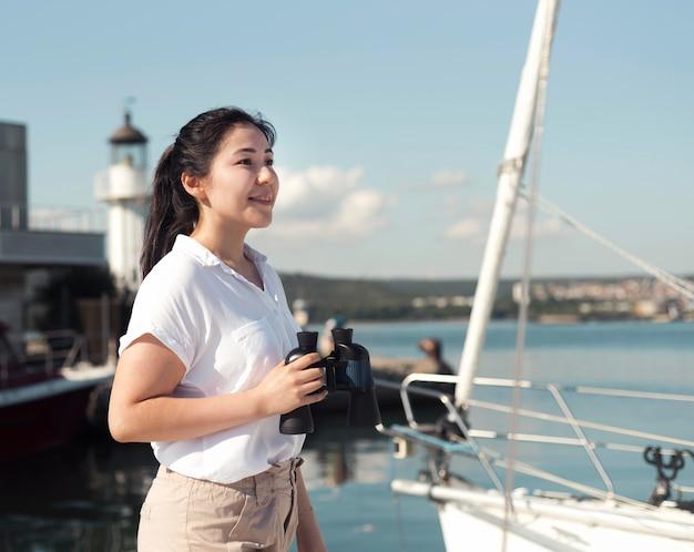 Вид сбоку женщина, держащая бинокль Бесплатные Фотографии