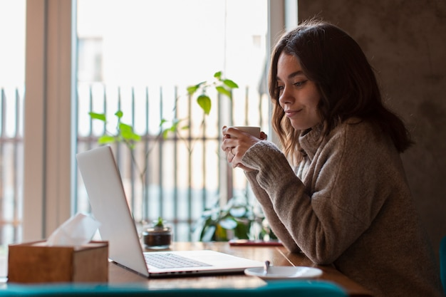 Side view of woman holding cup and looking at laptop Free Photo