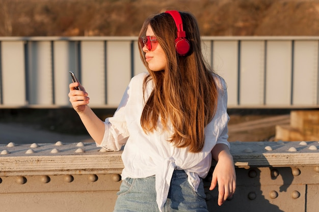 Side view of woman holding smartphone while wearing sunglasses and headphones Free Photo