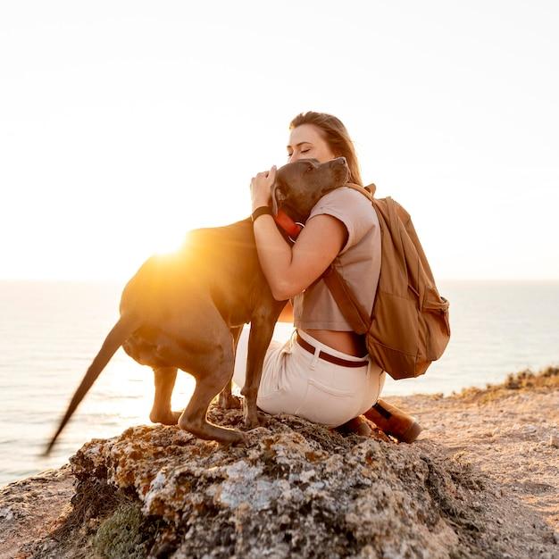 日没時に犬を抱き締める側面図の女性 無料写真