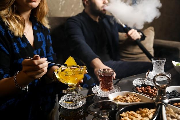 Вид сбоку женщина накладывает ананасовое варенье в блюдце с орехами и стакан чая на столе Бесплатные Фотографии