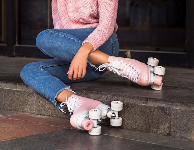 Side view of woman in jeans on stairs with roller skates Free Photo