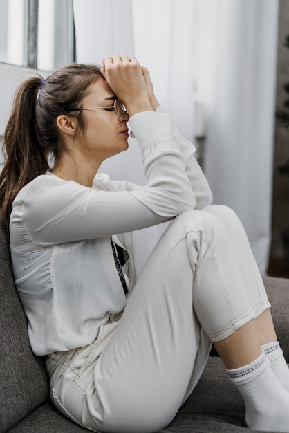 Donna di vista laterale che sembra triste mentre lavora da casa Foto Gratuite
