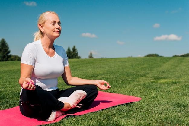 Вид сбоку женщина медитирует на природе Бесплатные Фотографии