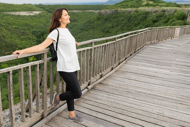 Side view of woman in nature posing on bridge Free Photo