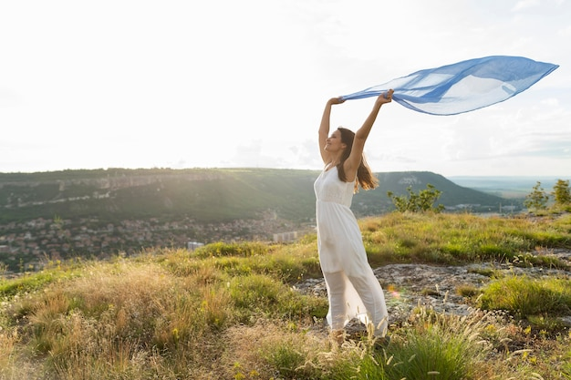 Side view of woman in nature with scarf in the wind Free Photo