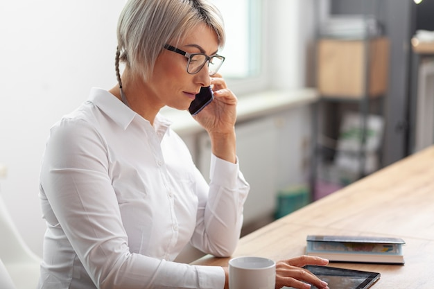 Side view woman at office talking over phone Free Photo