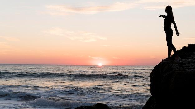 Вид сбоку женщина, указывающая на закат с копией пространства Бесплатные Фотографии