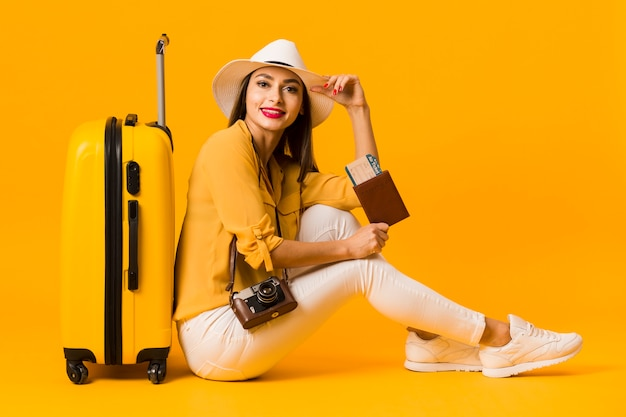 Side view of woman posing next to luggage while holding travel essentials Free Photo