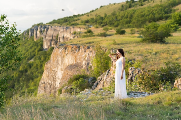 Side view of woman posing outdoors with mountain Free Photo