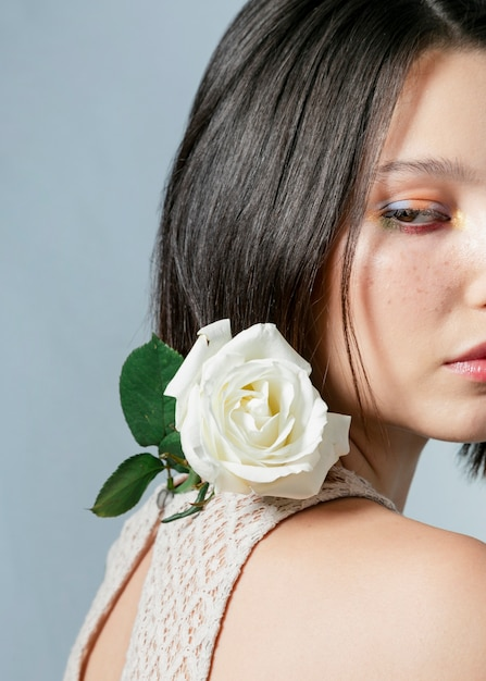 Side view of woman posing with white rose Free Photo