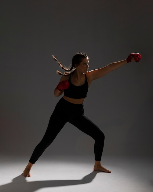 Side view woman punching with box gloves Free Photo