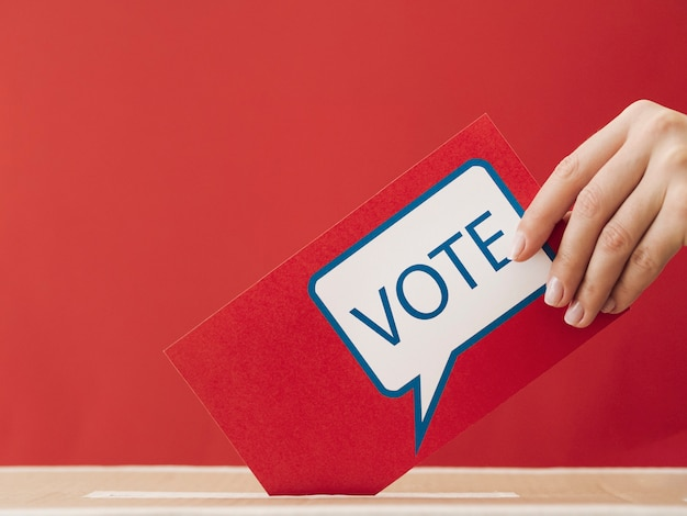 Женщина взгляда со стороны кладя красную карточку голосования в коробку Premium Фотографии