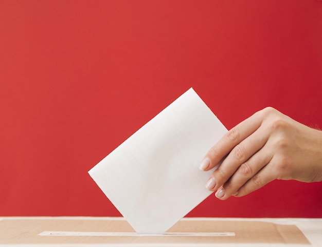 Side view woman putting a ballot in a box with red background Free Photo
