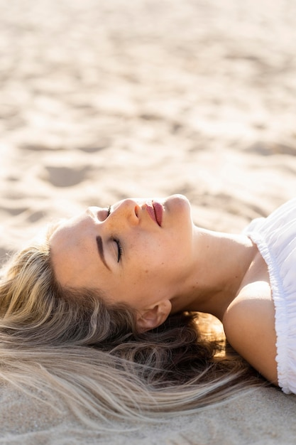 Side view of woman relaxing on beach sands Free Photo