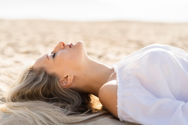 Side view of woman relaxing at the beach Free Photo