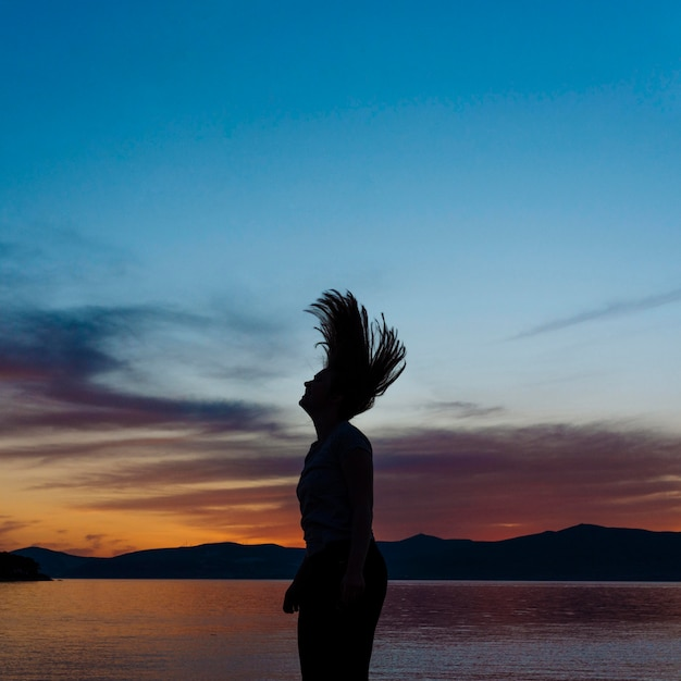 Side view of woman silhouette on the beach at sunset Free Photo