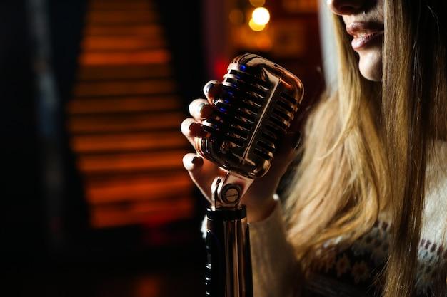 Вид сбоку женщина поет микрофон Бесплатные Фотографии