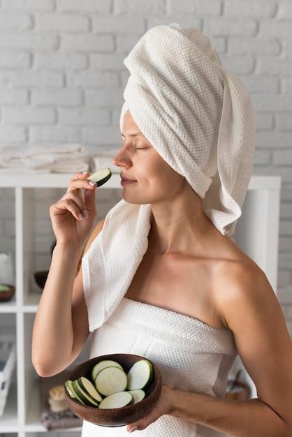 Vista laterale donna sentente l'odore di fetta di zucchine Foto Gratuite