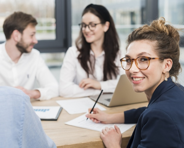 Side view of woman smiling while signing job contract Premium Photo