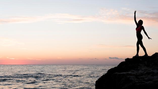 Donna di vista laterale in abiti sportivi in piedi su una costa con spazio di copia Foto Gratuite