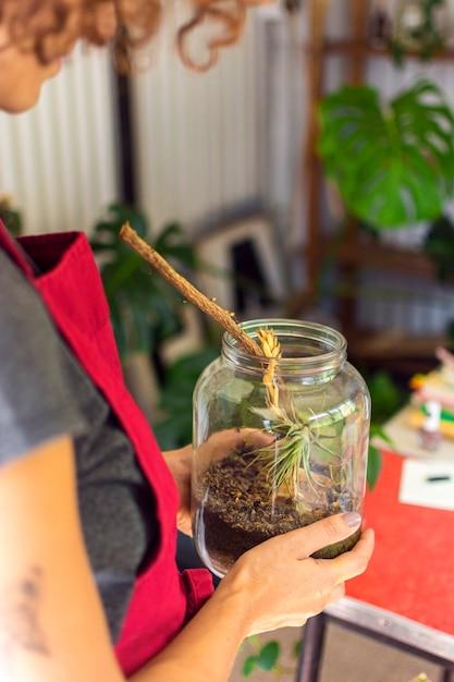 瓶の中の植物の世話をするサイドビュー女性 無料写真