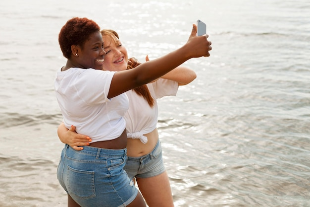 Side view of woman taking selfie at the beach Free Photo