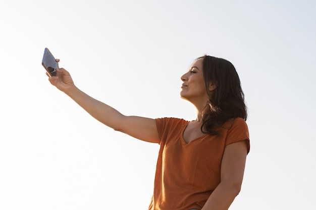 Side view of woman talking selfie outdoors Free Photo