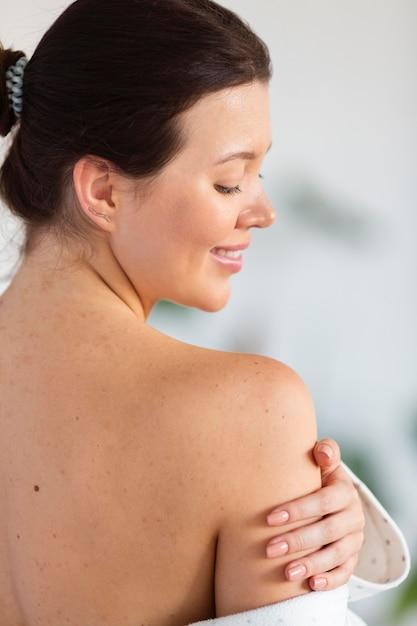 Vista laterale della donna che tocca la pelle morbida dopo la cura di sé Foto Gratuite