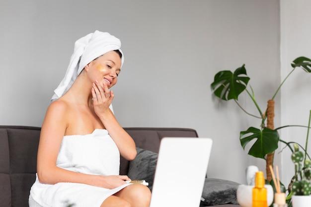 Vista laterale della donna in asciugamano che applica la cura della pelle Foto Gratuite