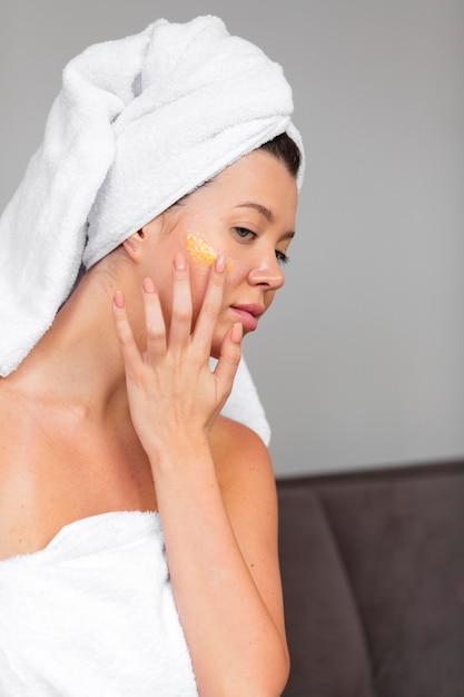 Vista laterale della donna in asciugamano utilizzando la cura della pelle Foto Gratuite