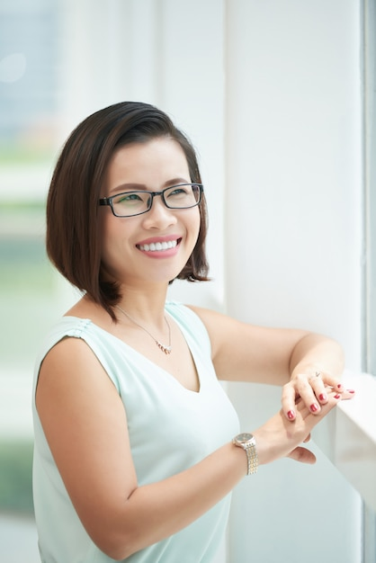 Side view of woman wearing elegant eye glasses looking at the window Free Photo