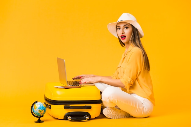 Side view of woman wearing hat while working on laptop on top of luggage Free Photo