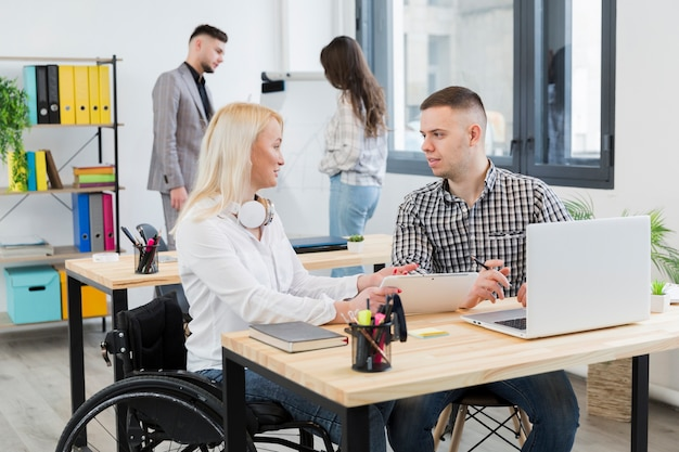 Vista laterale della donna in sedia a rotelle che discute con il collega al suo scrittorio Foto Gratuite