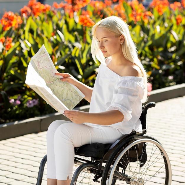Vista laterale della donna in sedia a rotelle guardando la mappa all'esterno Foto Gratuite