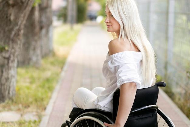 Vista laterale della donna in sedia a rotelle all'aperto con copia spazio Foto Gratuite