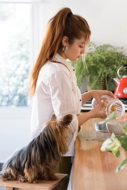 Вид сбоку женщина остроумие собака рядом на кухне Premium Фотографии