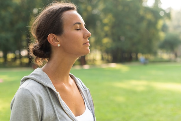 Side view woman with closed eyes outdoors Free Photo