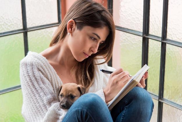 Женщина сбоку с собакой и тетрадью Бесплатные Фотографии