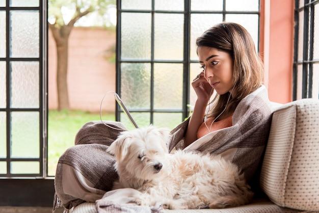Вид сбоку женщина с собакой на диване Бесплатные Фотографии